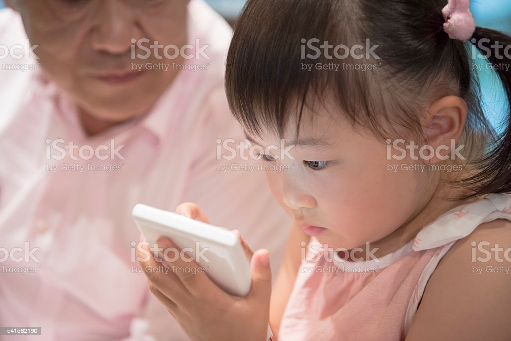 Close up of young Japanese girl concentrating on handheld device stock photo