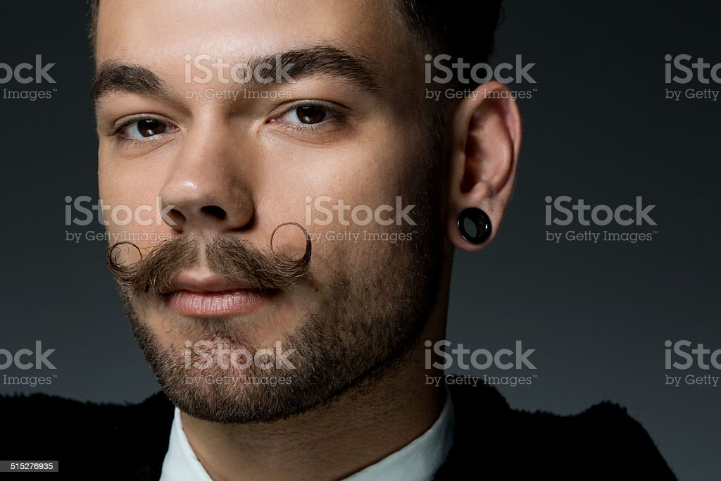 close up of young man with long moustaches stock photo