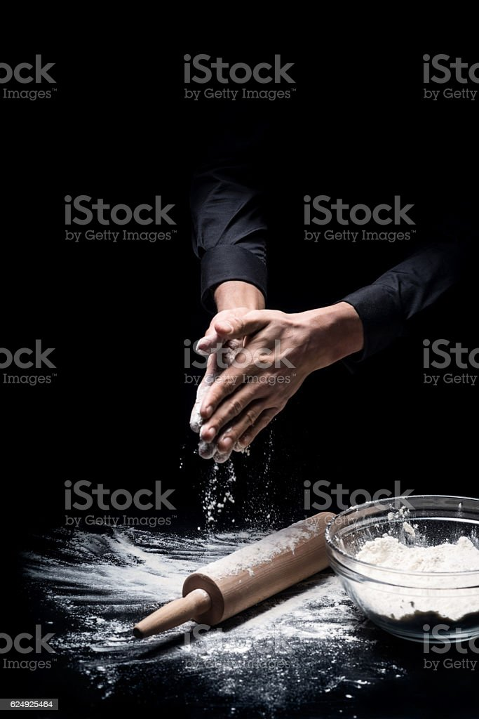 Close up of young mans hands preparing flour for baking stock photo