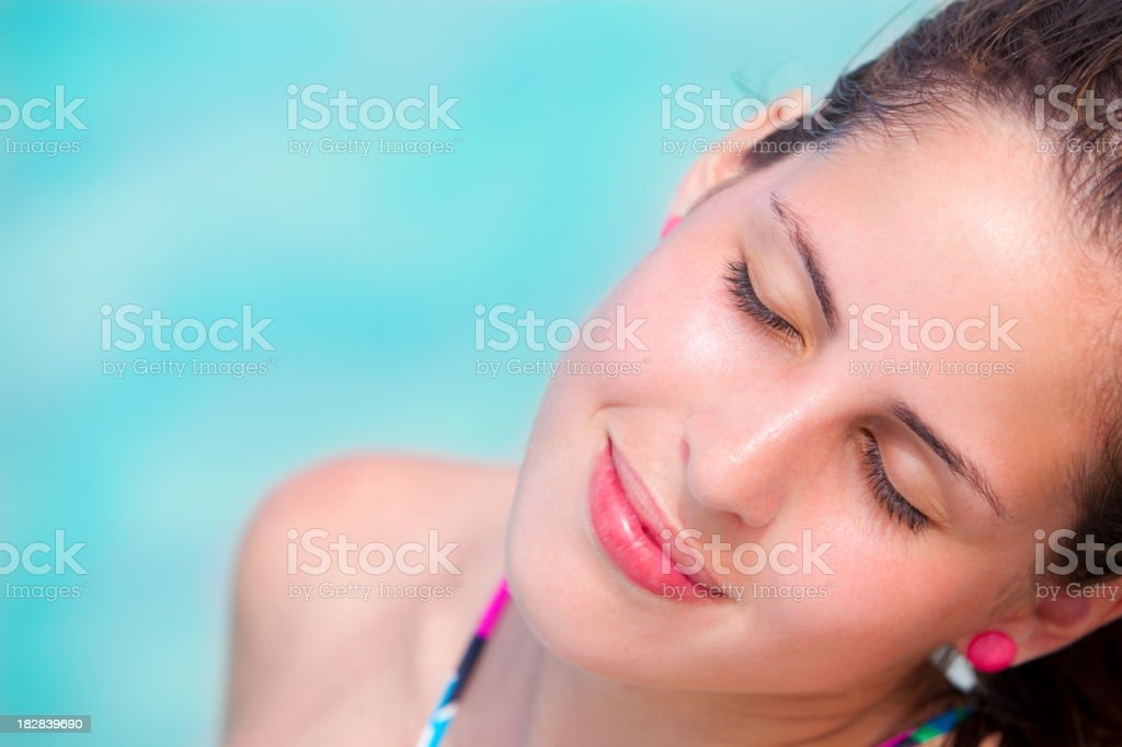 Close up of young pensive woman relaxing in turquoise beach stock photo