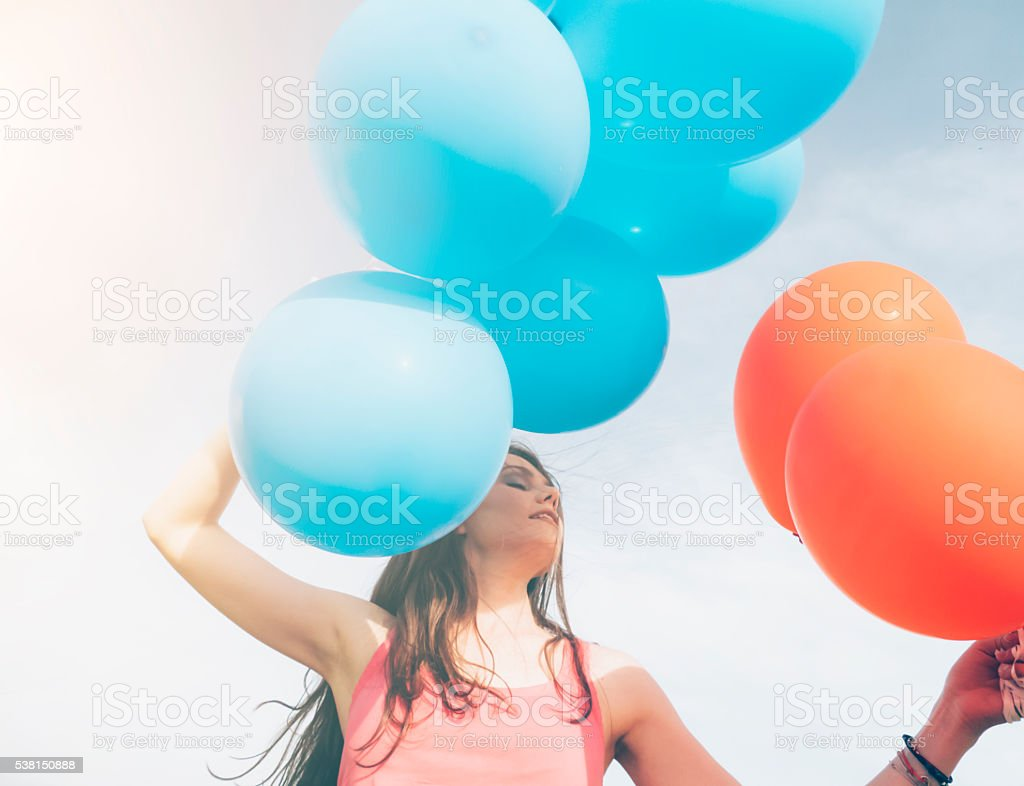 Close up of young woman holding a bunch of balloons stock photo