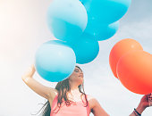 Close up of young woman holding a bunch of balloons