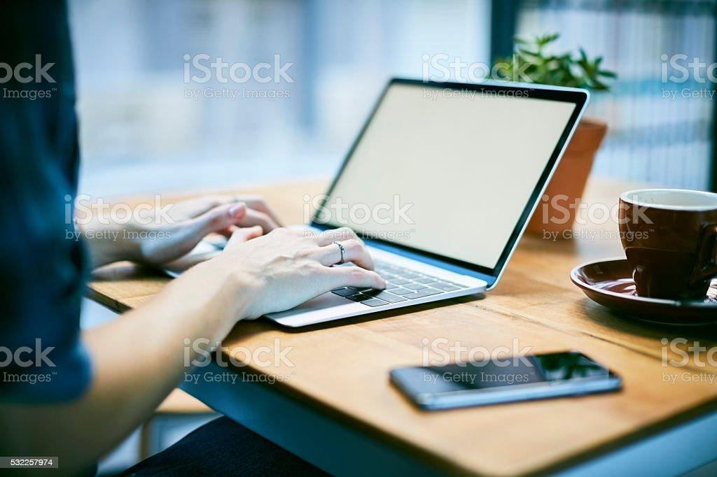 Close up of young woman using laptop in coffee shop stock photo