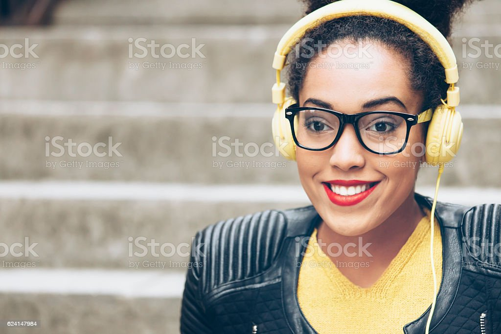 Close up of young woman with yellow headphones stock photo