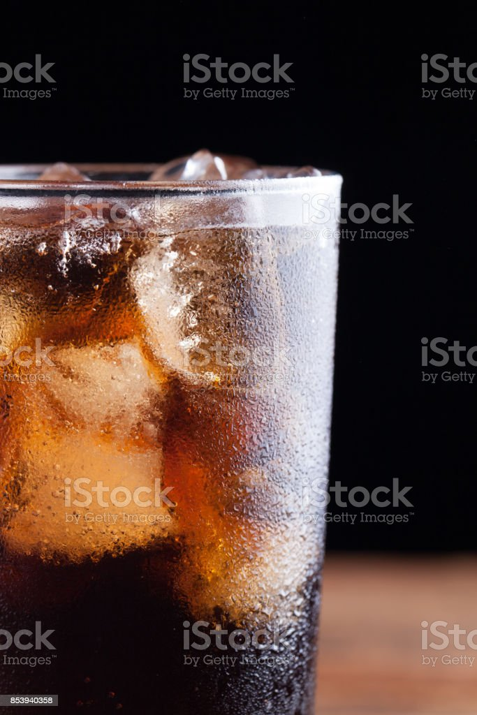 Close up on a cold refreshing soft drink with ice on a dark wooden background stock photo