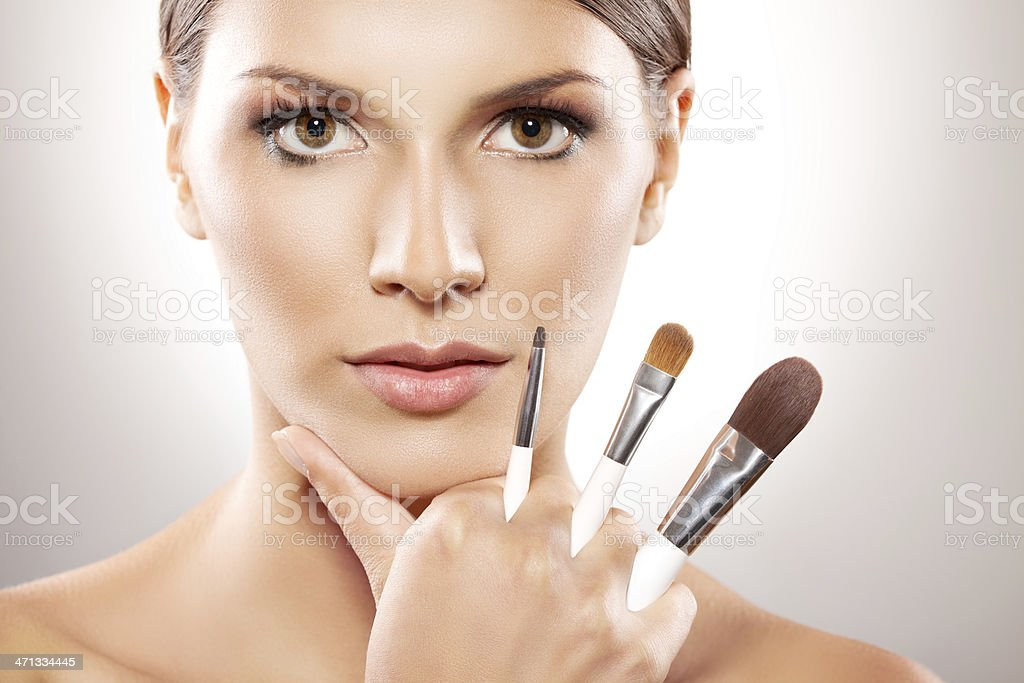 Close up on beautiful woman holding make-up brushes  stock photo
