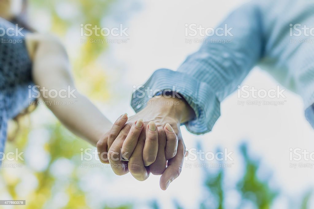 Close up on couple holding hands stock photo