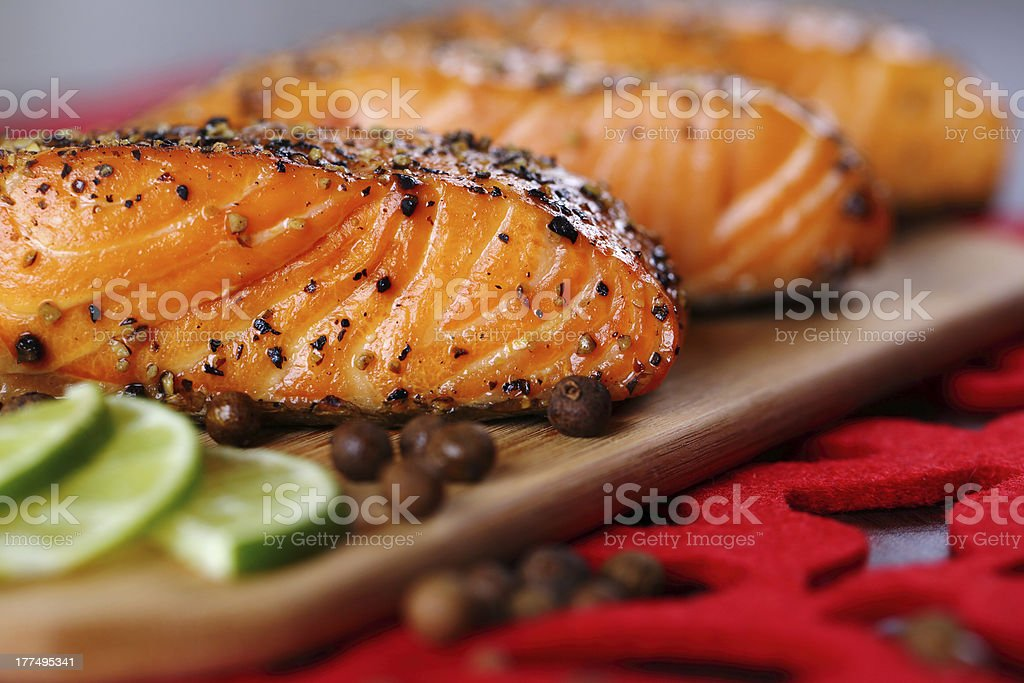 Close up on grilled salmon with pepper and lime. stock photo