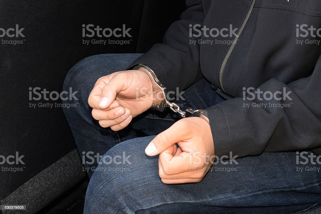 Close up on handcuffed hands of criminal stock photo