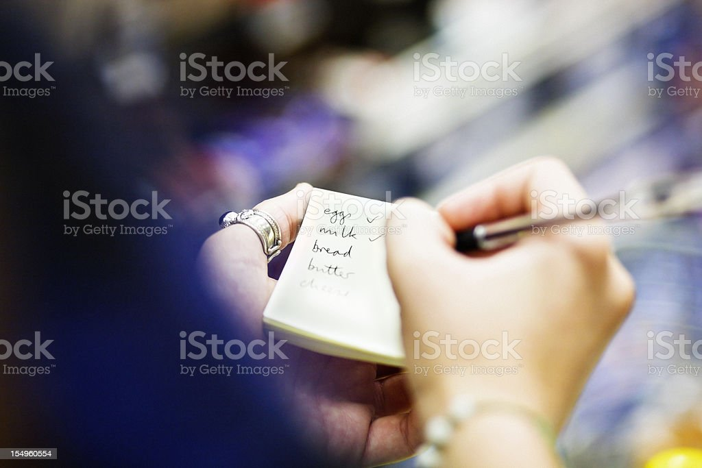 Close up on hands as woman checks shopping list royalty-free stock photo
