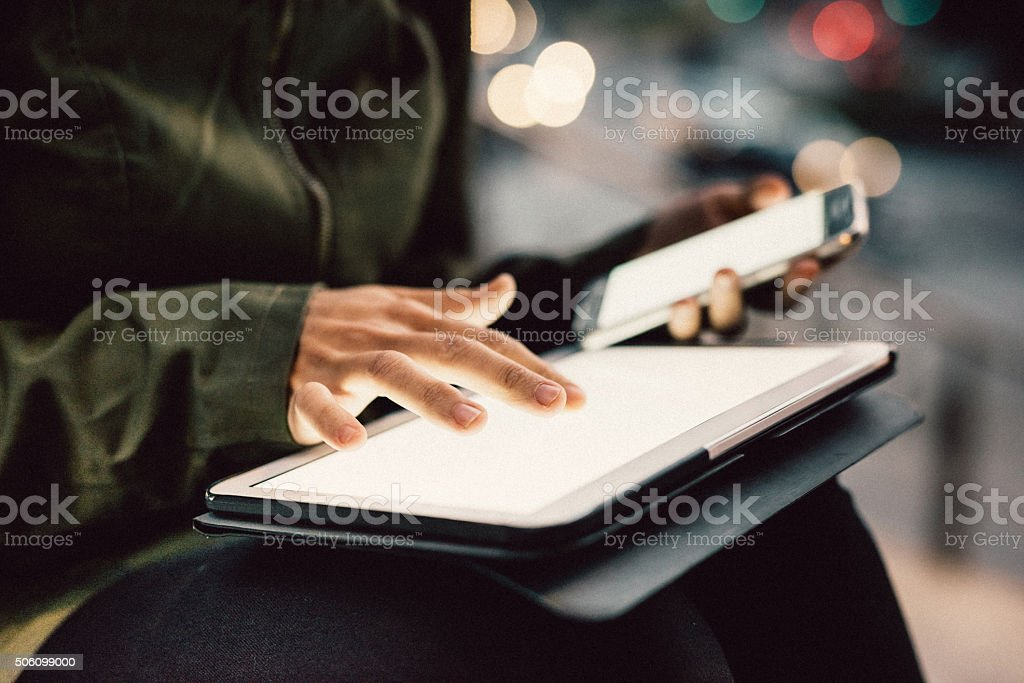 Close up on hands of woman using smartphone and tablet stock photo