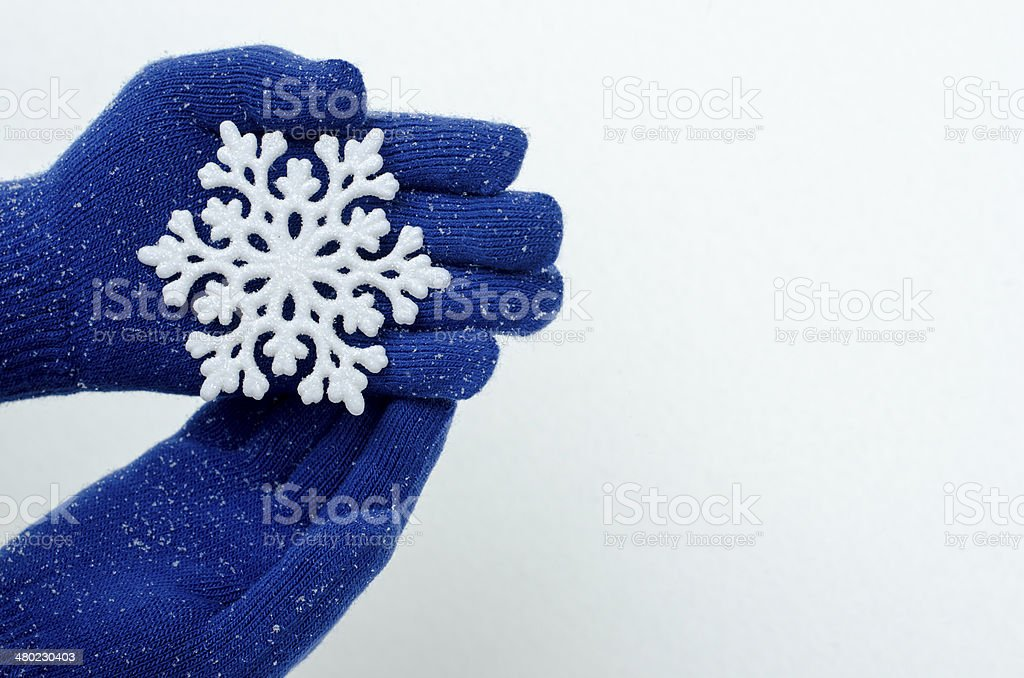 Close up on hands wearing blue gloves holding big snowflake. stock photo