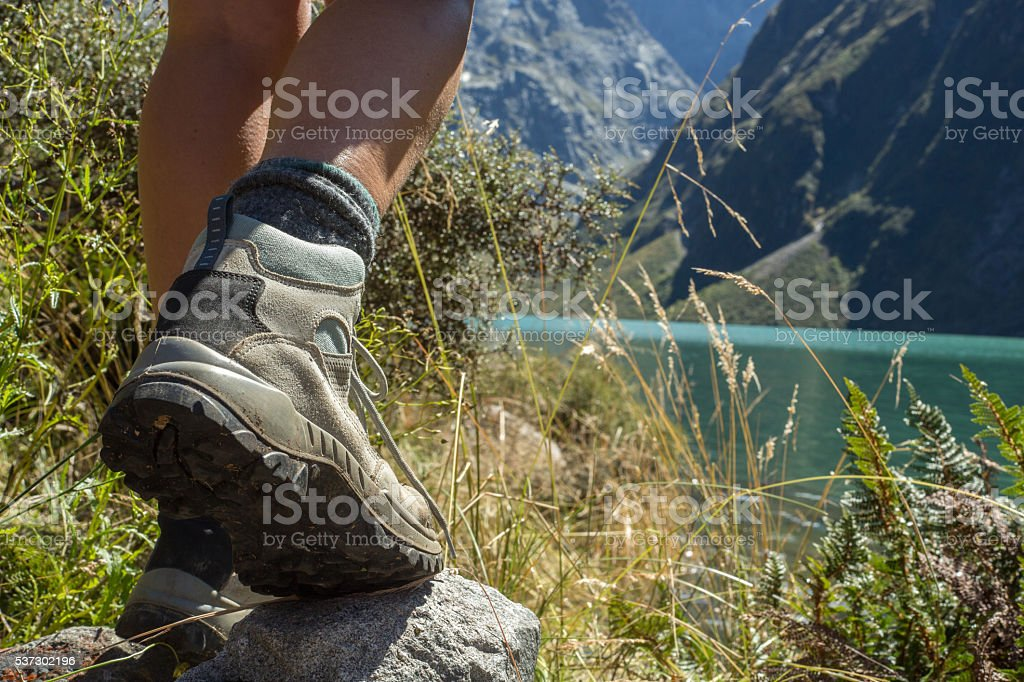 Close up on hiking boots standing on rock at lake stock photo