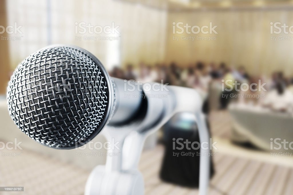 Close up on microphone with out-of-focus audience in background royalty-free stock photo