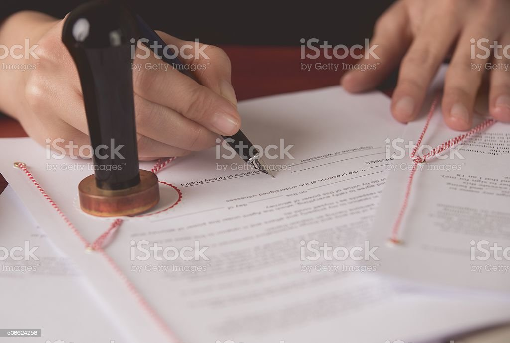 Close up on notaries public hand signing the testament stock photo