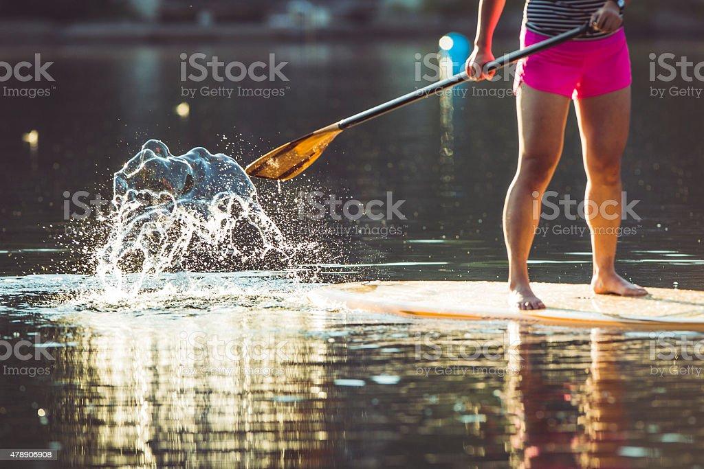 Close up on paddle boarding on calm lake during sunrise. stock photo