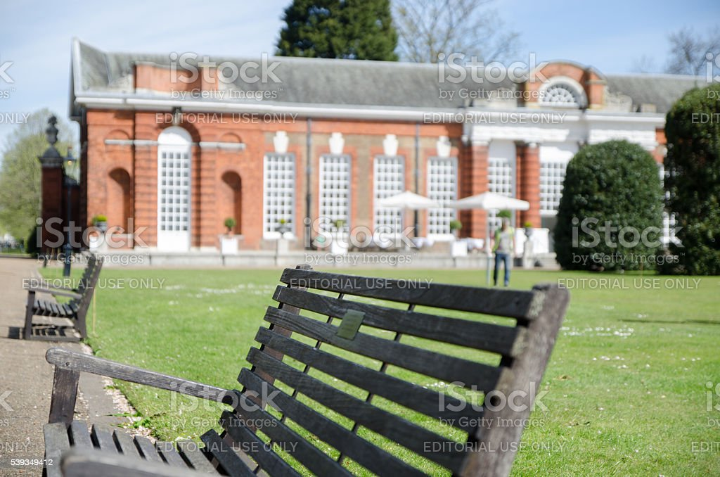 Close up on park bench with Orangerie Restaurant in background stock photo