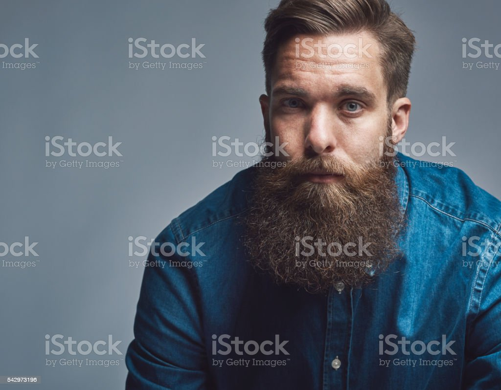 Close up on serious man in blue shirt and beard stock photo