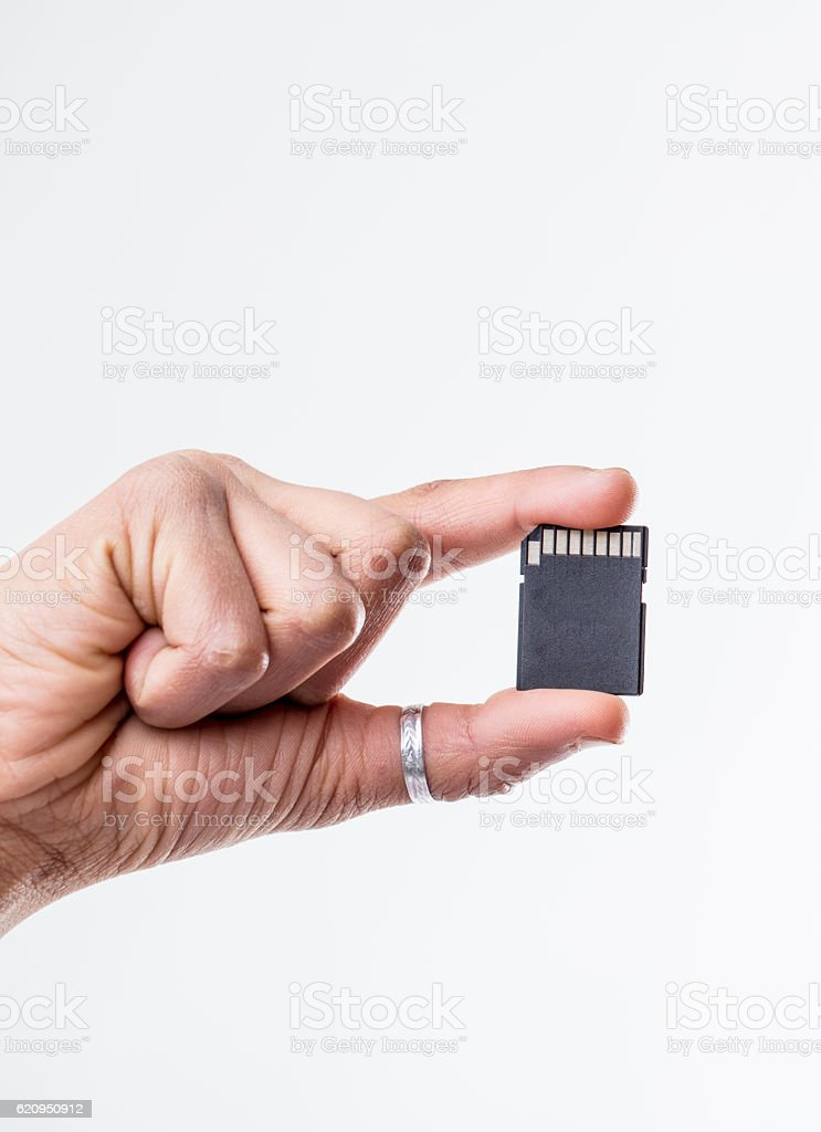 Close up on single hand holding blank SD card stock photo