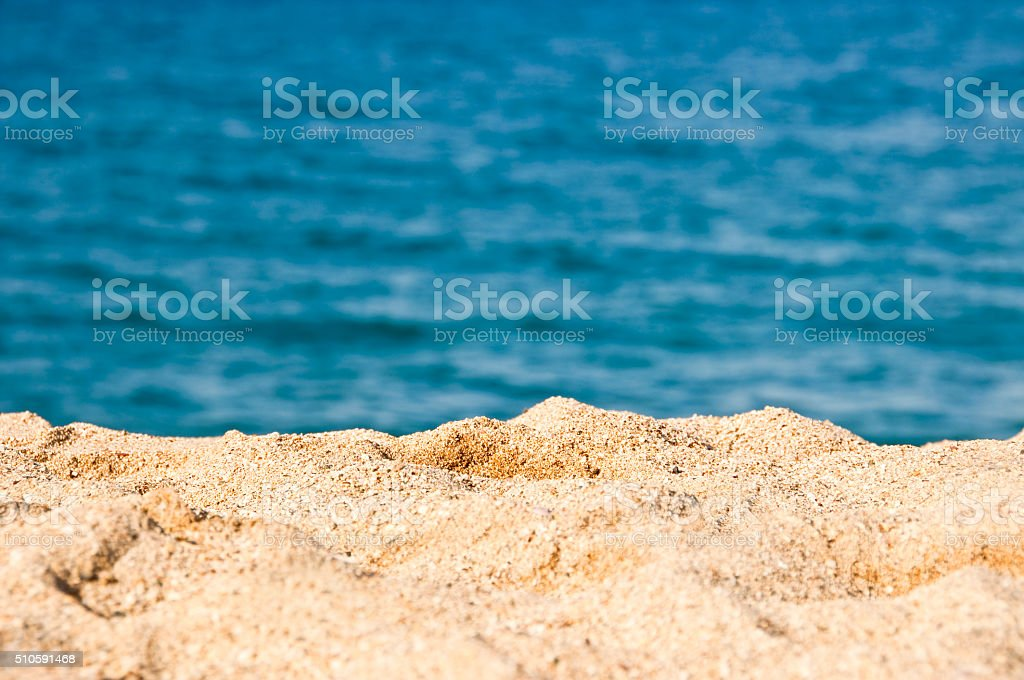 Close up on the sand of a beach, blue sea stock photo