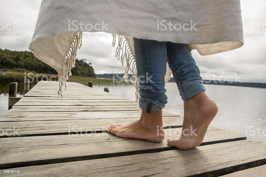 Close up on woman's feet standing on jetty above lake stock photo