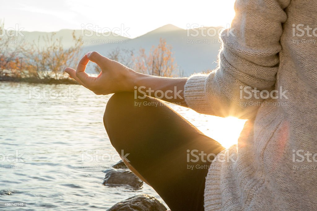 Close up on woman's hand exercising the lotus yoga position stock photo