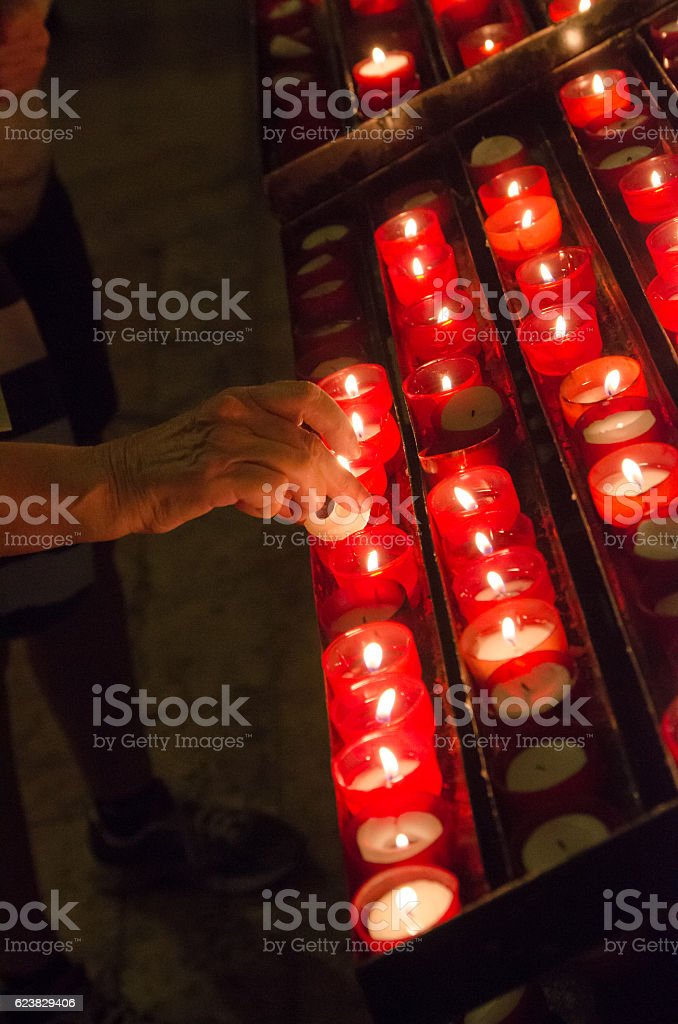 Close up on woman's hand lighting candle in church stock photo