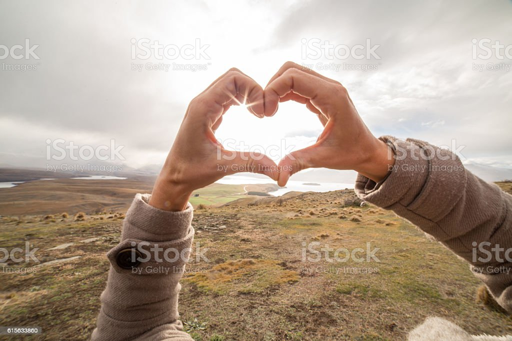 Close up on woman's hands making heart shape finger frame stock photo