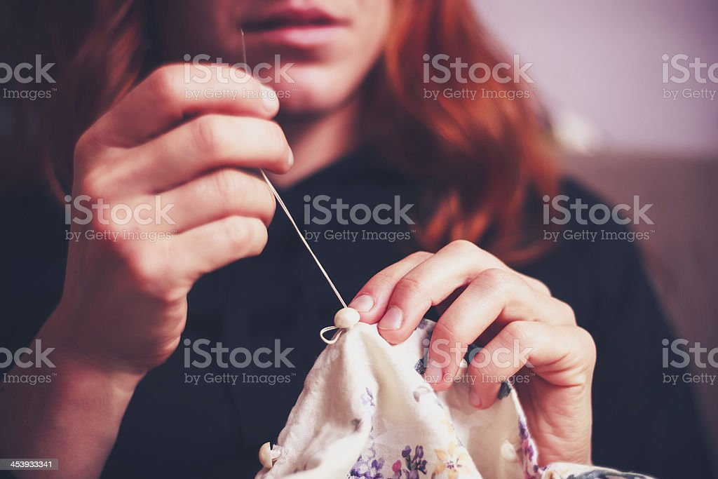 Close up on woman's hands sewing stock photo