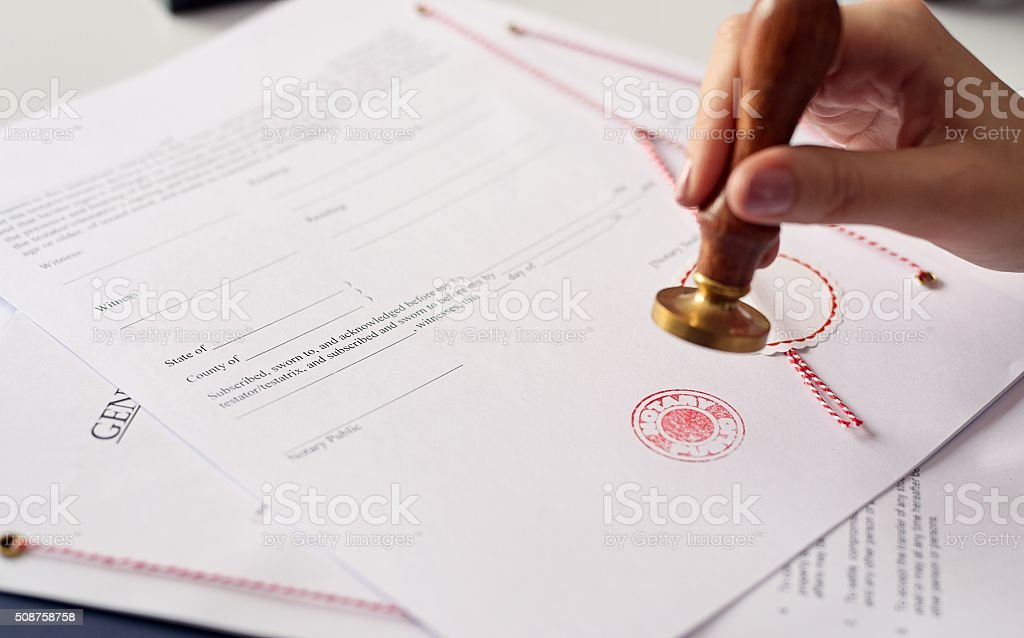 Close up on woman's notary public hand  stamping the document stock photo