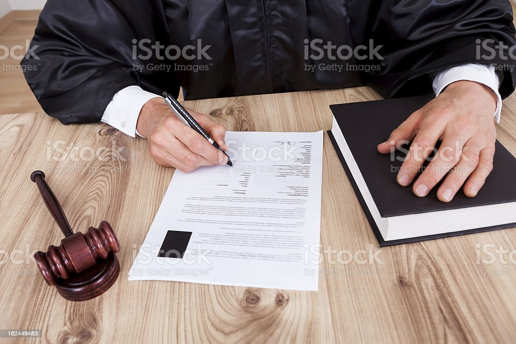 Close up photo of a robed judge signing a document stock photo