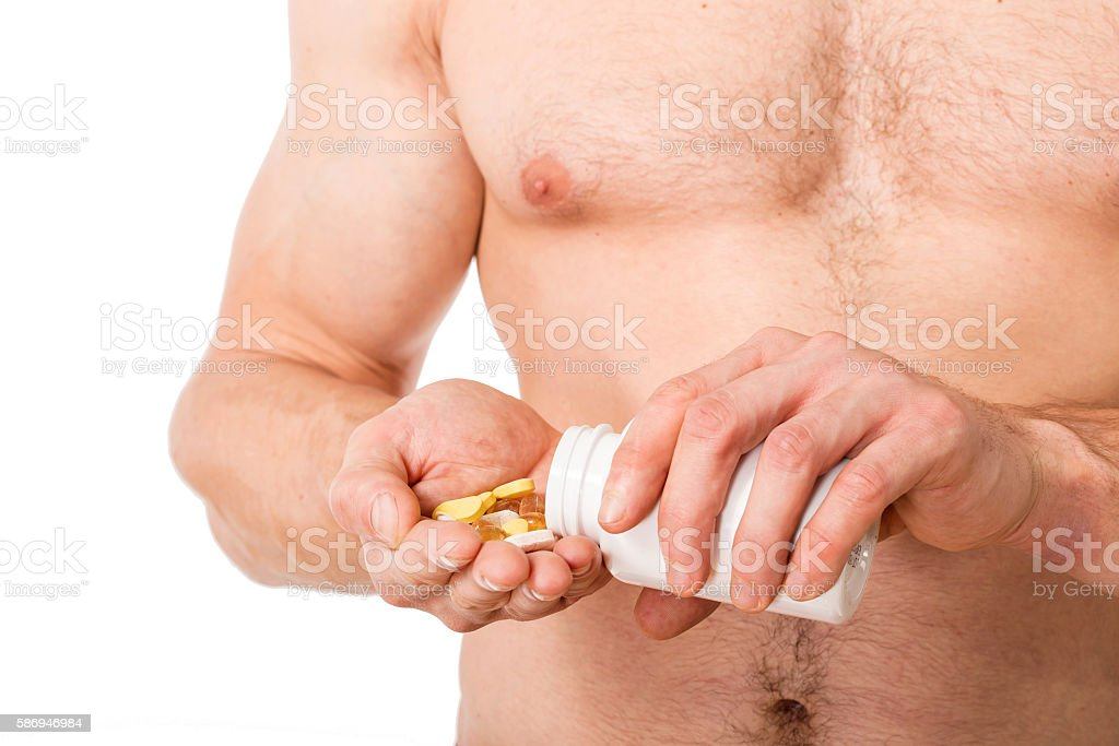 close up photo of athletic man holding some pills stock photo