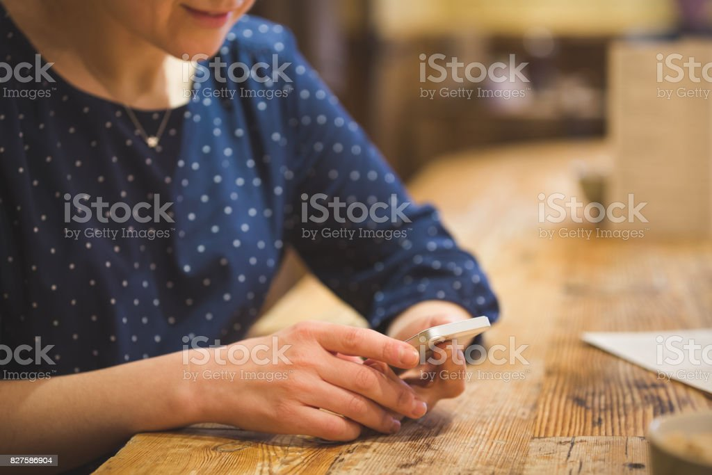 Close up photo of beautiful young woman sitting cozy at wooden table. Girl using  touch screen smartphone. Typing on the telephone. stock photo