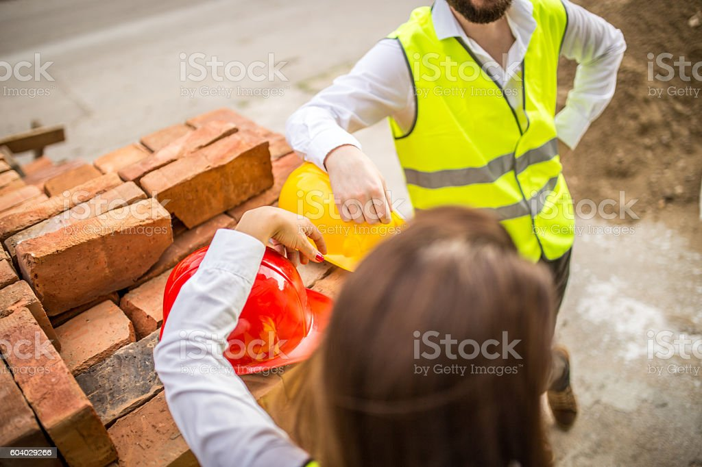 Close up photo of engineers hands with hardhat stock photo