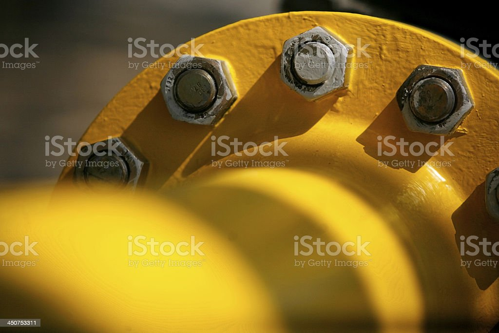 Close up photo of grey bolts on yellow pipe royalty-free stock photo