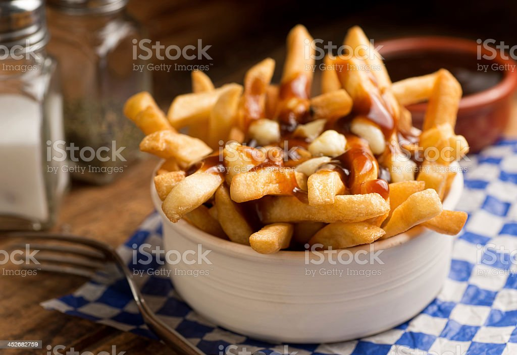 Close up photo of poutine in a white bowl with fork stock photo