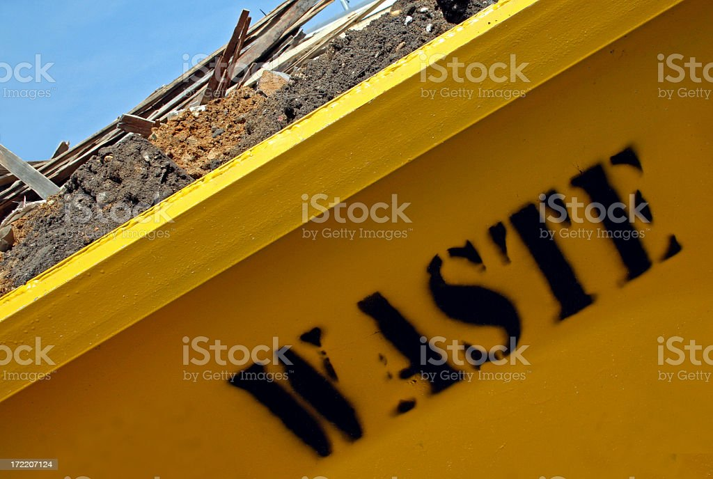 Close up photo of yellow construction dumpster reading WASTE royalty-free stock photo