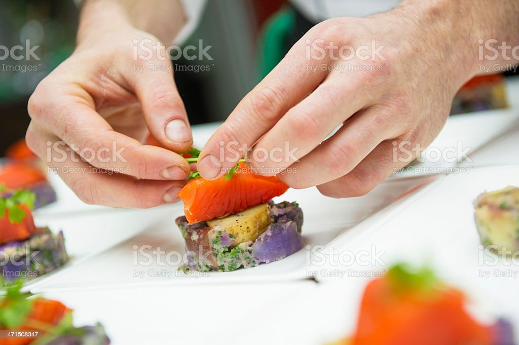 A close up photograph of hands preparing sushi stock photo