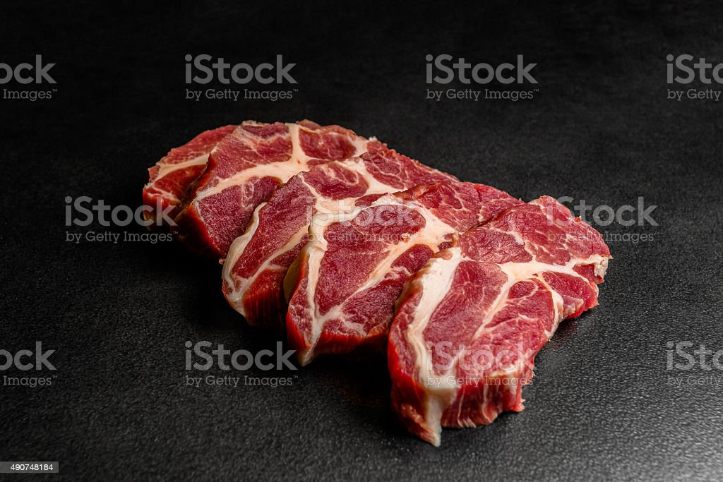 Close up pieces of raw pork on black background stock photo