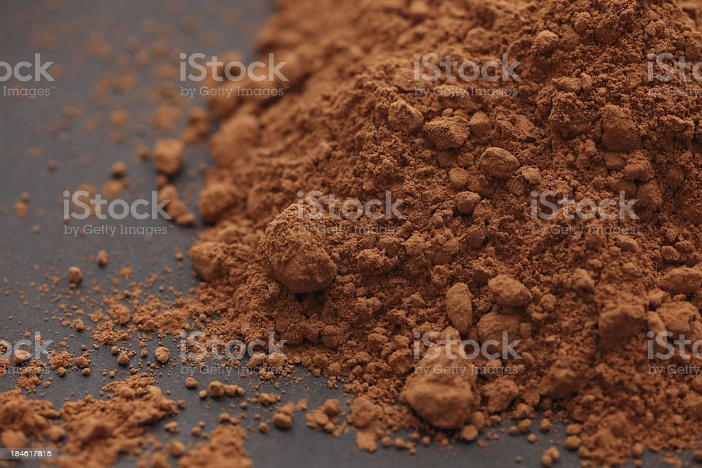 Close up pile of cocoa powder on a black surface stock photo