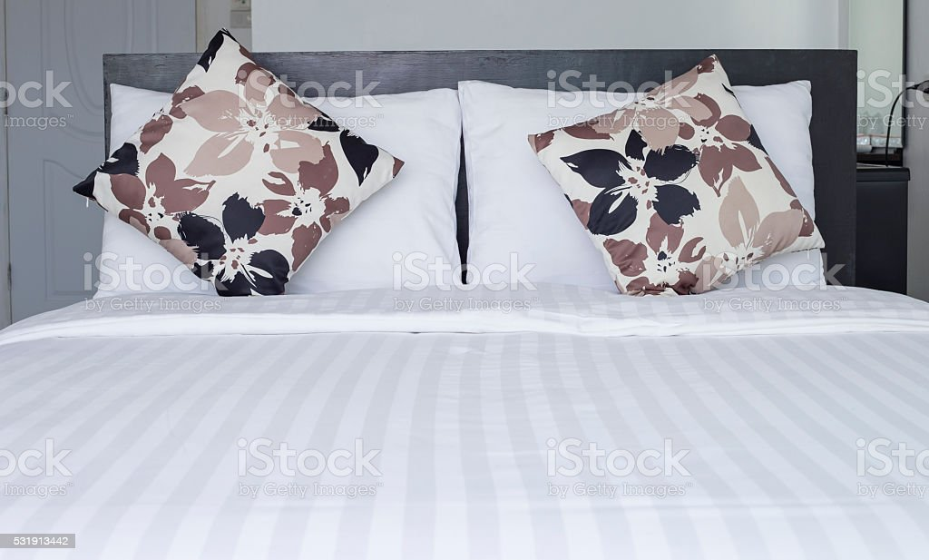 Close up pillow on white bedding sheets stock photo