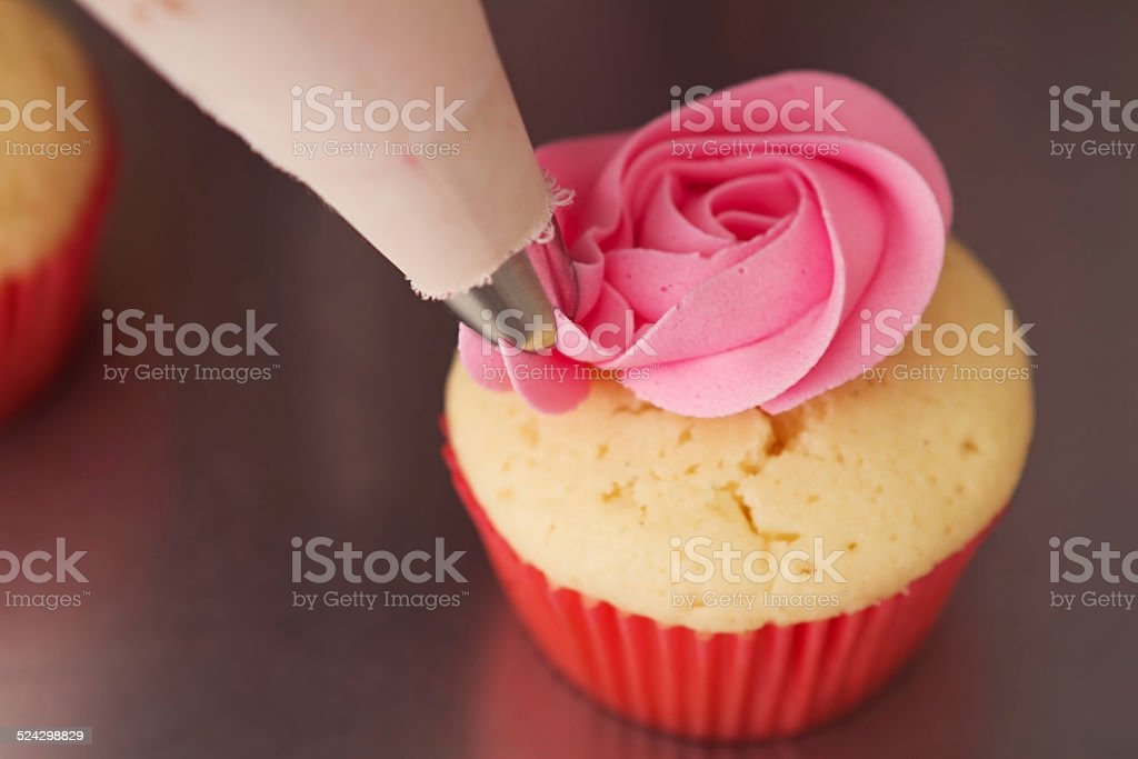 Close up pink rose frosted cupcake being piped Horizontal stock photo