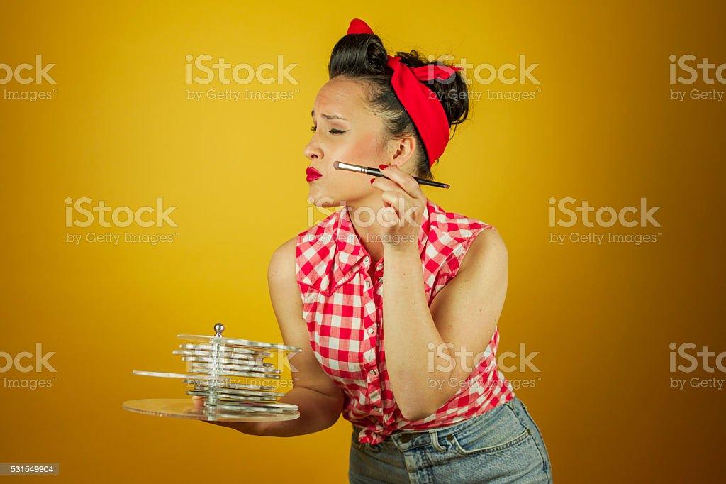 Close up portrait beautiful pin up girl putting on makeup stock photo