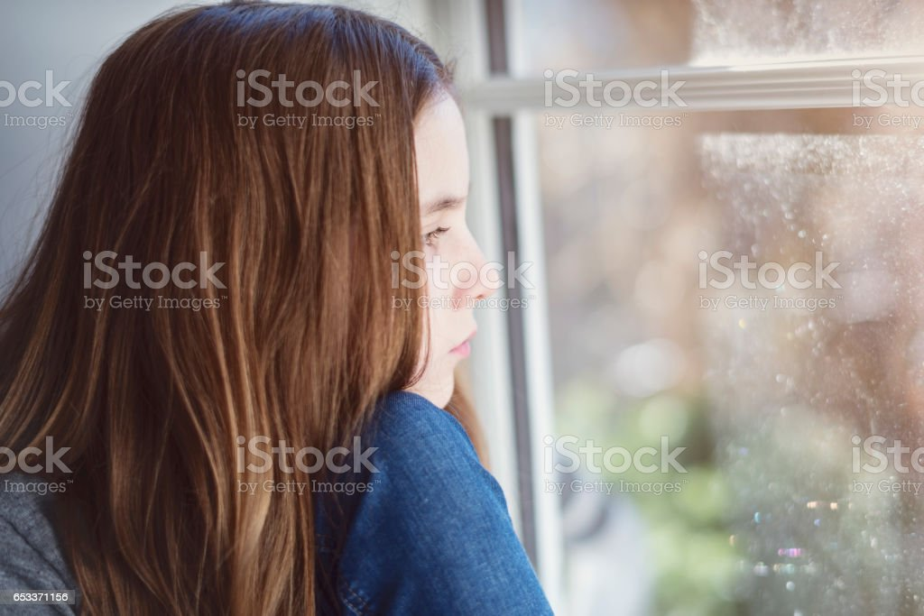 Close Up Portrait of a Lonely Twelve Year Old Girl Gazing Out Of a Window stock photo