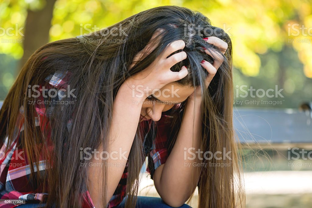 Close up portrait of a sad woman sitting on bench stock photo