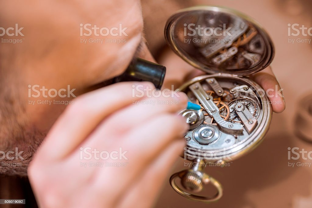 Close up  portrait of a watchmaker at work. stock photo