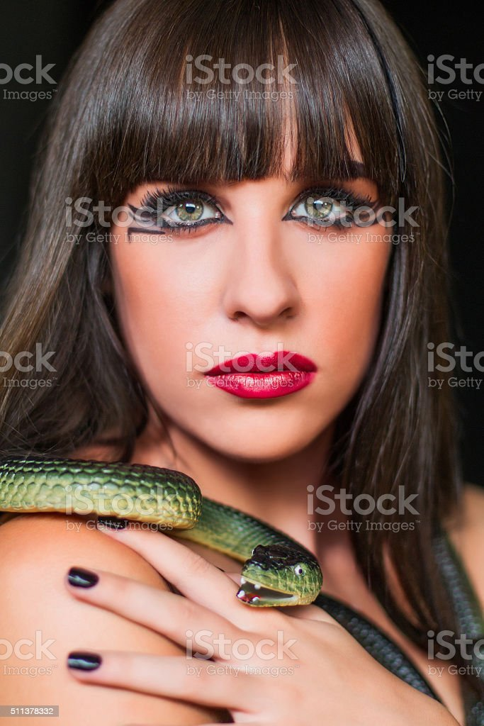 Close up portrait of beautiful girl with snake, black hair stock photo
