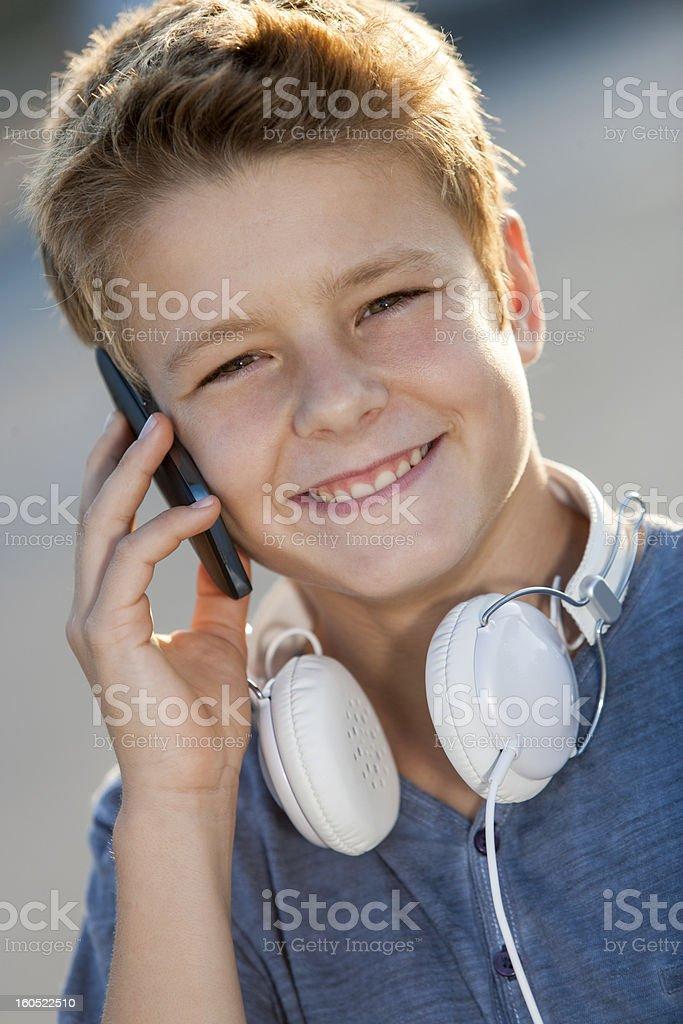 Gros plan portrait de garçon parler au téléphone à l'extérieur. photo libre de droits