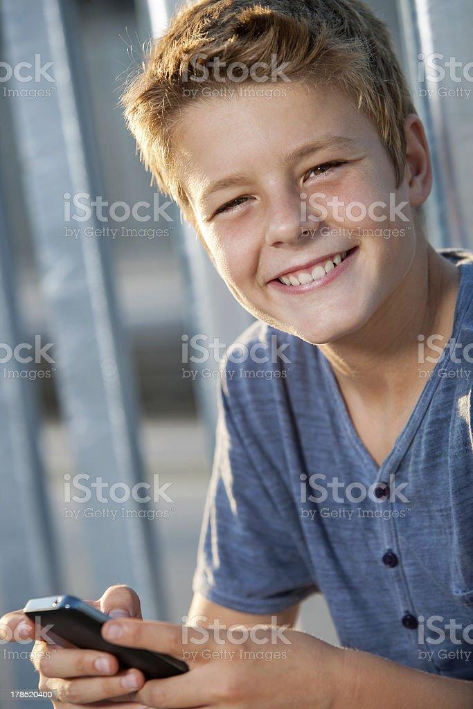 Gros plan portrait de garçon avec téléphone en plein air. photo libre de droits