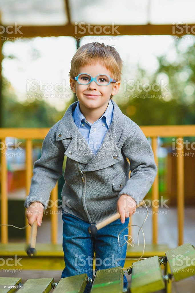 Close up portrait of cute boy playing xylophone outdoor stock photo